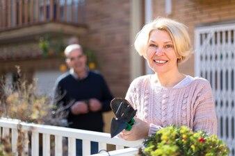 Hogere vrouw die op terras tuiniert
