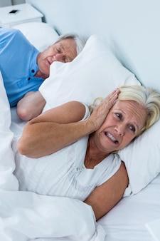 Hogere vrouw die oren behandelt terwijl man het snurken