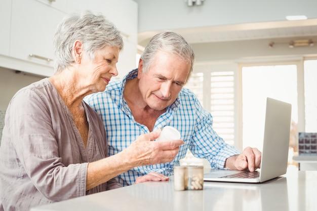 Hogere vrouw die pillen tonen aan echtgenoot met laptop