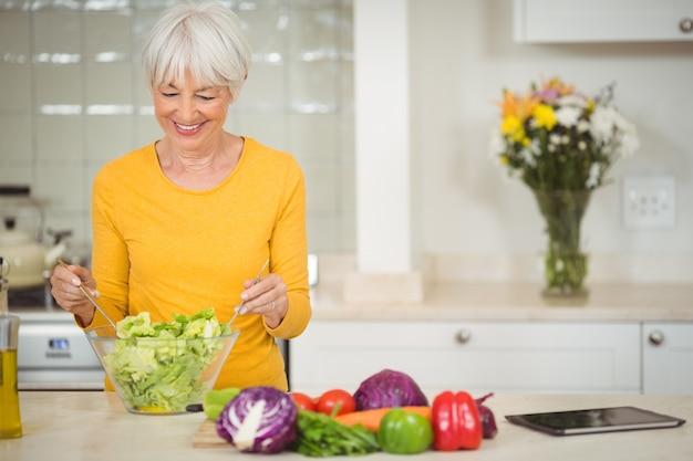 Hogere vrouw die plantaardige salade voorbereidt