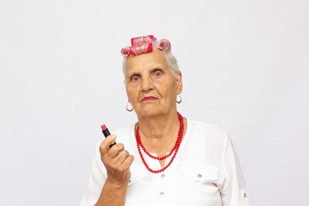 Hogere vrouw die roze lippenstift aanbrengt