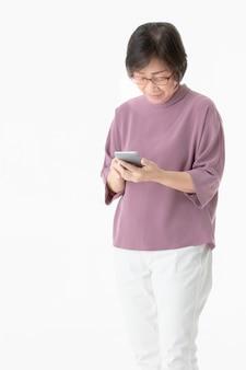 Hogere vrouw die slimme telefoon met behulp van.