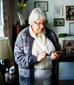 Hogere vrouw die smartphone gebruikt
