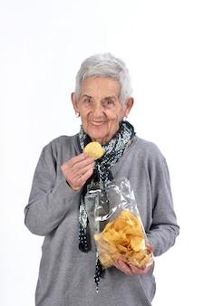Hogere vrouw die spaanders op wit eet