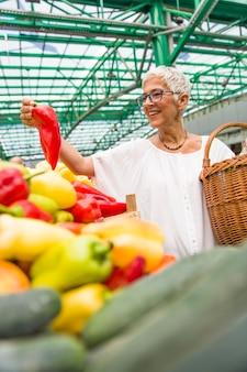 Hogere vrouw die spaanse pepers kopen bij de markt