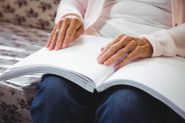 Hogere vrouw die te lezen braille gebruikt