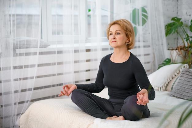 Hogere vrouw die terwijl het zitten in lotusbloempositie uitoefent. actieve rijpe vrouw die uitrekkende oefening in woonkamer thuis doet.