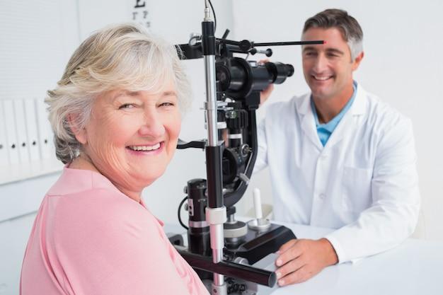 Hogere vrouw die terwijl het zitten met opticien glimlacht