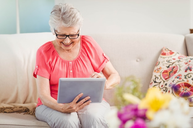 Hogere vrouw die terwijl thuis het gebruiken van digitale tablet glimlacht