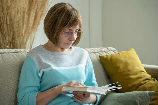 Hogere vrouw die thuis alleen een boek leest