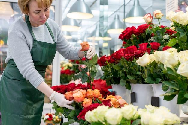 Hogere vrouw die voor mooie bloemen zorgt