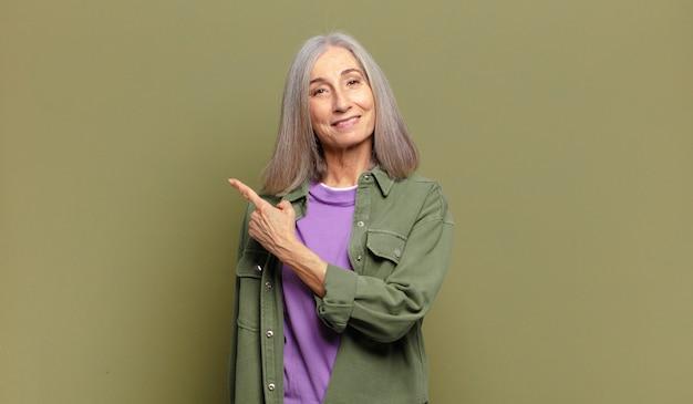 Hogere vrouw die vrolijk glimlacht, zich gelukkig voelt en naar de zijkant en naar boven wijst, voorwerp in exemplaarruimte toont