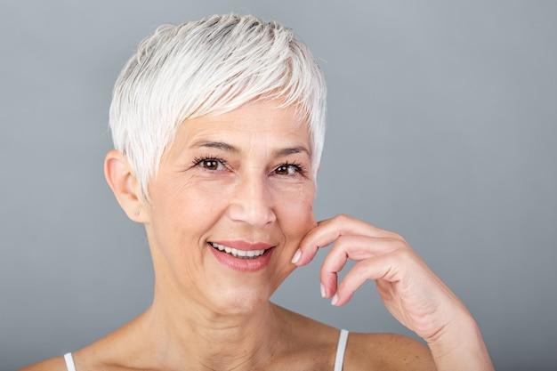 Hogere vrouw die wangen trekt om zachtheid te voelen en camera te bekijken. schoonheidsportret van het gelukkige rijpe vrouw glimlachen met handen op wang geïsoleerd over grijze achtergrond. verouderingsproces en huidconcept.