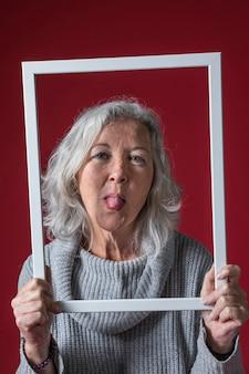 Hogere vrouw die witte kadergrens houdt die uit haar tong steekt tegen rode achtergrond