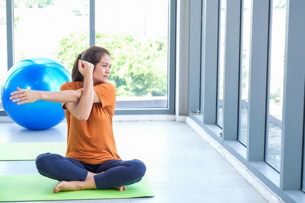 Hogere vrouw die yoga in een studio uitvoert