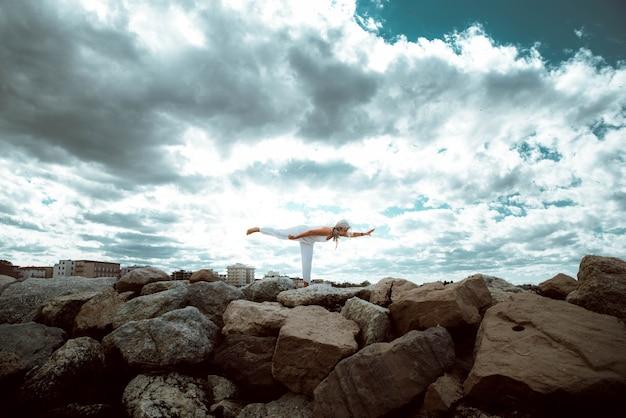 Hogere vrouw die yogaoefening doet bij strand