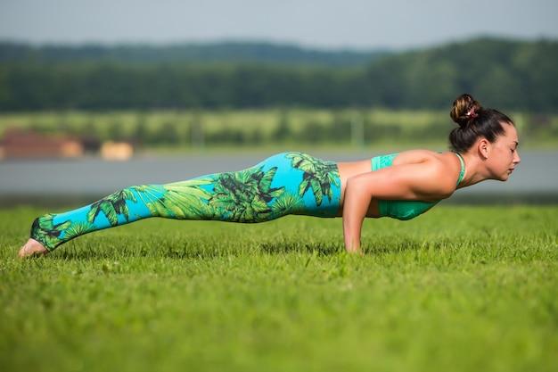 Hogere vrouw die yogaoefeningen met erachter bergen doet