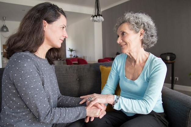 Hogere vrouw en haar dochter die en handen spreken spreken