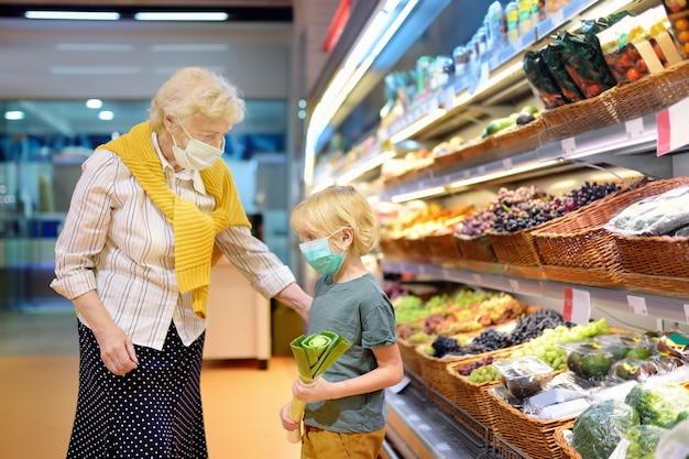 Hogere vrouw en haar kleinkind die wegwerp medisch masker dragen bij het winkelen