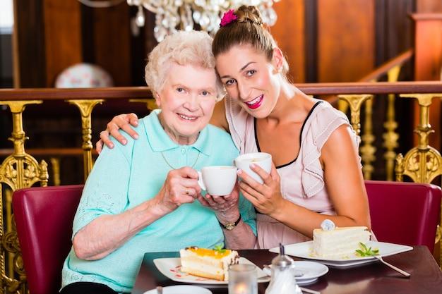 Hogere vrouw en kleindochter bij koffie in koffie