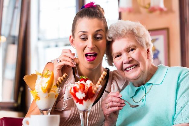Hogere vrouw en kleindochter die pret hebben die roomijsijscoupe in koffie eten