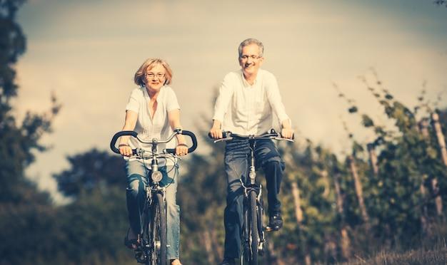 Hogere vrouw en man die fiets in de zomer gebruiken