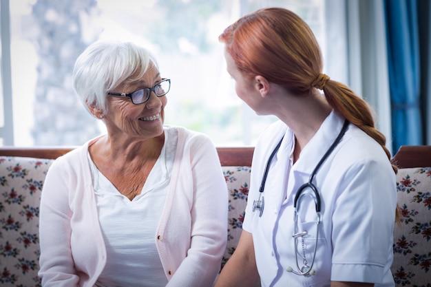 Hogere vrouw en vrouwelijke arts die in woonkamer op elkaar inwerken