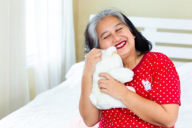 Hogere vrouw gelukkig met teddybeer