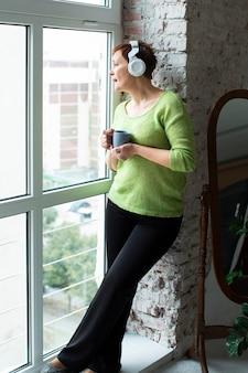 Hogere vrouw het luisteren muziek en het kijken op venster