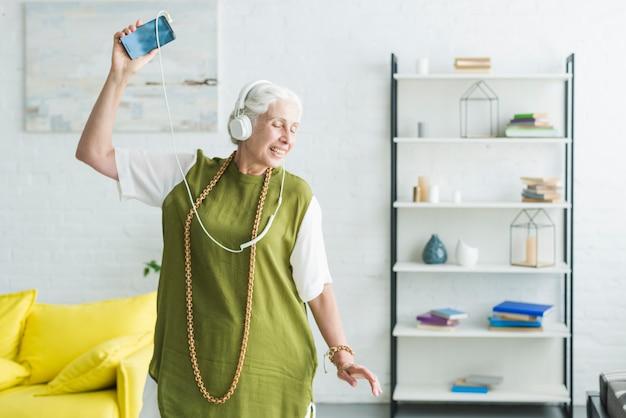 Hogere vrouw het luisteren muziek op hoofdtelefoon die in de woonkamer dansen