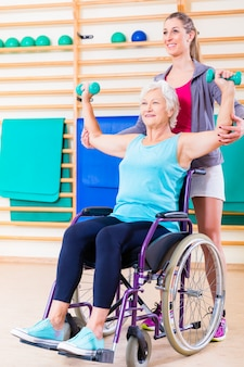 Hogere vrouw in rolstoel die fysieke therapie doet
