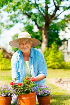 Hogere vrouw met bloemen in tuin