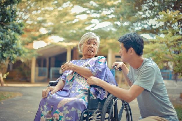 Hogere vrouw met dochter; verpleegster die hogere vrouw op rolstoel behandelt