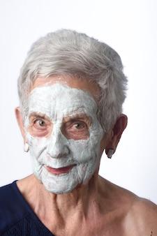 Hogere vrouw met facian masker op wit