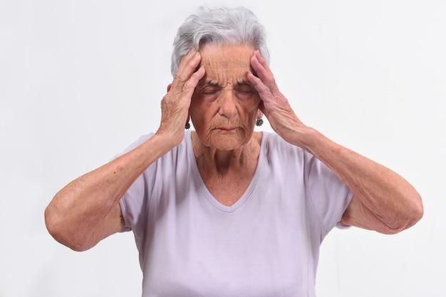 Hogere vrouw met hoofdpijn op witte achtergrond
