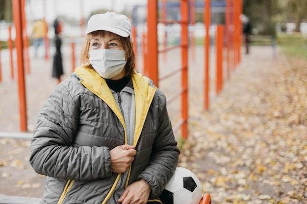 Hogere vrouw met medisch masker en voetbal in openlucht
