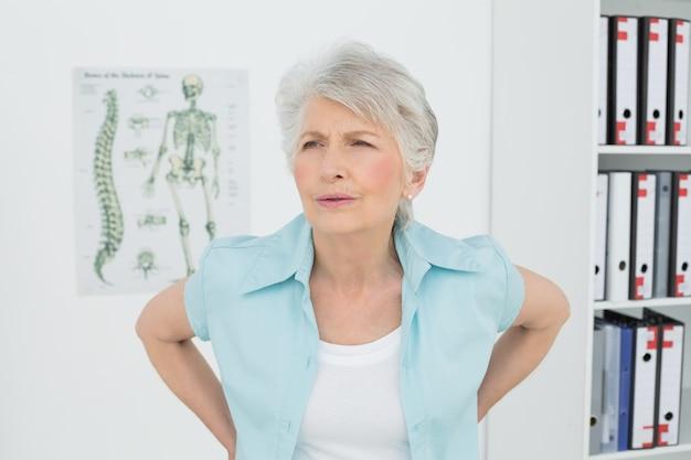 Hogere vrouw met rugpijn in medisch bureau
