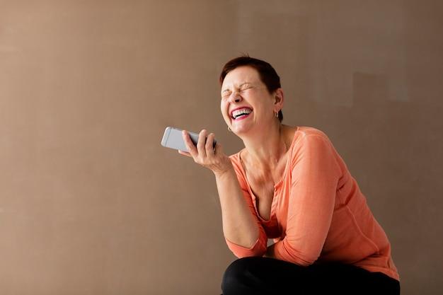 Hogere vrouw met telefoon die een goede tijd heeft