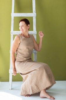 Hogere vrouw op een ladder die weg kijkt