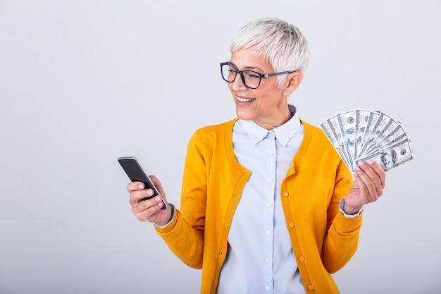Hogere vrouw op haar smartphone en holdingsgeld