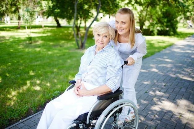 Hogere vrouw op rolstoel met verzorger buitenshuis