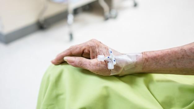 Hogere vrouwelijke patiënt opgenomen three way-connector voor intraveneuze infusie