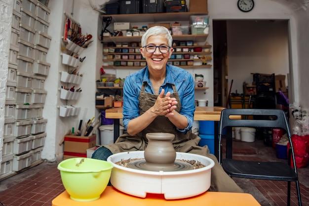 Hogere vrouwelijke pottenbakker die aan aardewerkwiel werken terwijl het zitten in haar workshop