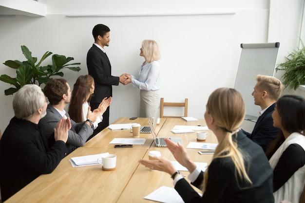 Hogere vrouwelijke werkgever die handenschudden afrikaanse werknemer bevorderen terwijl het team toejuicht