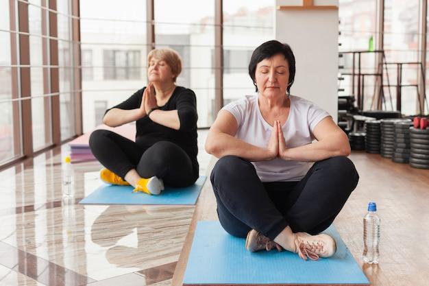 Hogere vrouwen bij gymnastiek die yoga doen