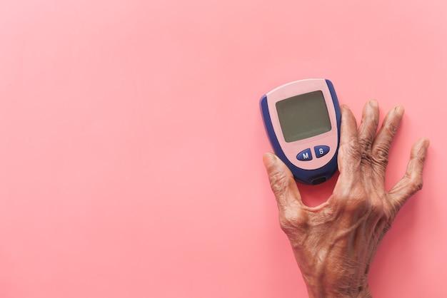 Hogere vrouwen die diabetische meetinstrumenten op roze houden.