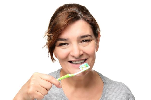 Hogere vrouwen schoonmakende tanden op wit