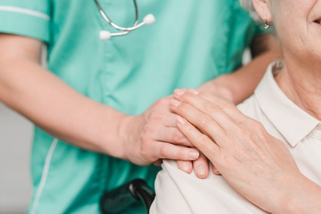 Hogere vrouwenpatiënt wat betreft vrouwelijke verpleegstershand op schouder
