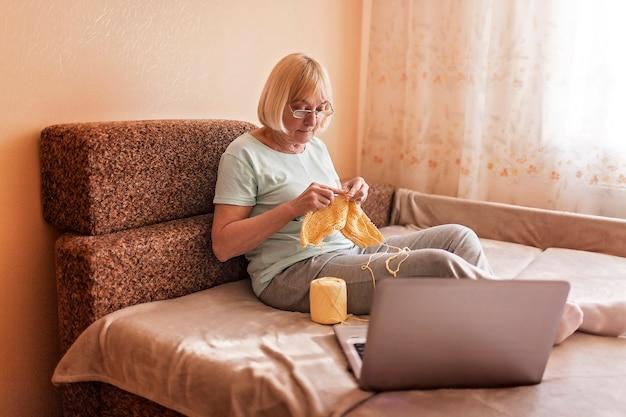Hogere vrouwenzitting op bank en thuis het breien van een wollen sweater