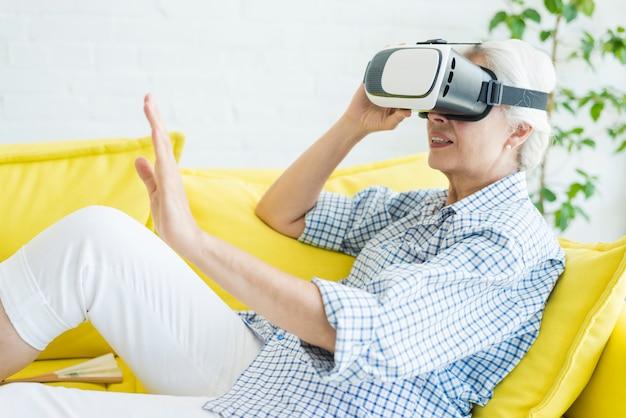 Hogere vrouwenzitting op gele bank die virtuele werkelijkheidsglazen gebruikt